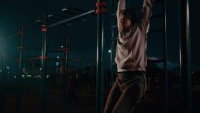 Los ciudadanos masculinos están entrenando en el área juguetona del parque de la ciudad en la noche metrajes
