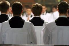Los clérigos jovenes del seminario durante masa Foto de archivo libre de regalías