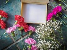 Los claveles coloridos con el espacio de la caja y de la copia en el granito emergen Imagenes de archivo