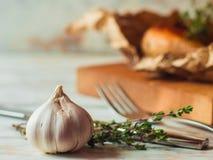 Los clavos de ajo en fondo de madera del vintage asaron el pollo encendido en fondo Imagen de archivo libre de regalías