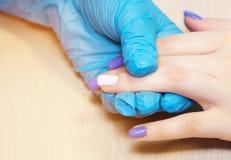 Los clavos de la mujer natural sana del primer en sal?n de belleza Clavos del cliente de la pintura de la mano del manicuro Recub imagen de archivo