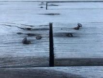 Los clavos oxidados se pegan en el tablón de madera para el tablero de la junta dos juntos fotografía de archivo