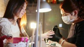 Los clavos profesionales cuidan en el proceso, cosmetólogo con la máscara en los guantes negros que hacen los clavos al cliente f almacen de metraje de vídeo