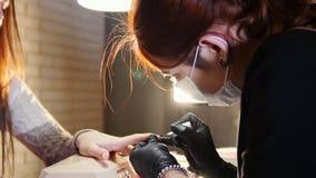 Los clavos profesionales cuidan en el proceso, cosmetólogo con la máscara en los guantes negros que hacen los clavos al cliente f metrajes