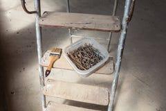 Los clavos y los tornillos están en la caja plástica y el cepillo está en el paso de madera de la escalera Foto de archivo libre de regalías