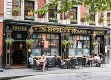 Los clientes beben la cerveza en las tablas fuera de la barra de Sherlock Holmes en Londres Imágenes de archivo libres de regalías