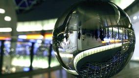 Los clientes desconocidos caminan en una alameda de compras moderna Visión torcida a través de la esfera de cristal almacen de metraje de vídeo