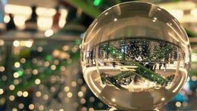 Los clientes en la Navidad y el Año Nuevo adornaron la alameda de compras Visión torcida a través de la bola de cristal almacen de metraje de vídeo