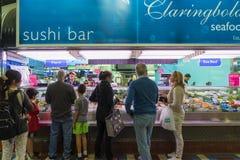 Los clientes hacen cola para arriba para comprar mariscos en una tienda foto de archivo