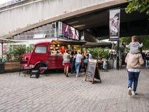 Los clientes visitan la furgoneta roja brillante del bocado, la orilla del río, Londres Imagen de archivo libre de regalías