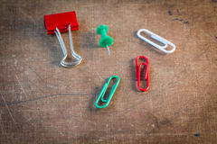 Los clips de papel coloridos fijaron en viejo fondo de papel Fotografía de archivo