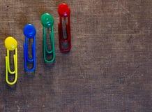 Los clips de papel coloridos fijaron en viejo fondo de papel Imagen de archivo