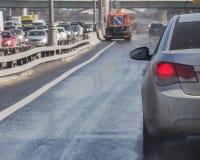 Los coches circundan la máquina de la limpieza en la carretera El agua salpica f Imagenes de archivo