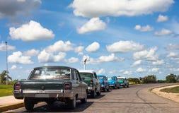 Los coches clásicos de Cuba alineados drived en el camino Foto de archivo