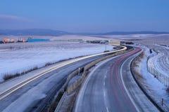 Los coches coloreados se arrastran en la carretera en el crepúsculo de la mañana Foto de archivo libre de regalías