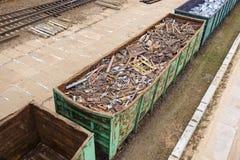Los coches con la chatarra de la basura están en el ferrocarril en la plataforma foto de archivo