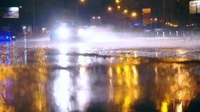 Los coches conducen en los charcos grandes en el camino de la noche en la ciudad, charcos del espray dispersan de debajo las rued almacen de video