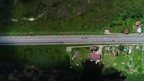 Los coches conducen en la carretera, situada en el campo almacen de video
