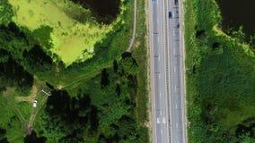 Los coches conducen en la carretera, situada en el campo metrajes