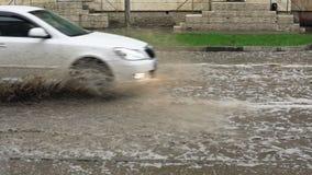 Los coches conducen en un camino inundado en la lluvia, cámara lenta almacen de metraje de vídeo