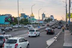 Los coches conducen a lo largo de la carretera con un puente, Ucrania, Kyiv editorial 08 03 2017 fotos de archivo