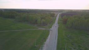 Los coches conducen a lo largo de la carretera que corre entre los bosques y los campos metrajes