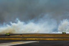 Los coches de bomberos acometen para luchar el fuego en el aeropuerto Fotografía de archivo