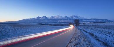 Los coches de la noche se encienden en el camino por mañana del invierno Imagen de archivo