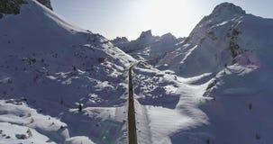 Los coches de siguiente aéreos delanteros en el camino en valle nevoso en Valparola pasan Puesta del sol o salida del sol soleada almacen de metraje de vídeo