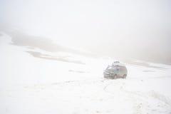 Los coches de viajeros en el camino de la nieve de la montaña ajardinan coche en un paso de montaña, pico del jeep 4x4 del soport imagenes de archivo