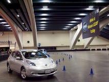 Los coches en el movimiento en Nissan Leaf prueban área de conducción Foto de archivo