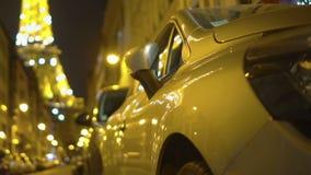 Los coches en la calle de París en noche se encienden con la torre Eiffel chispeante detrás, empañado almacen de video