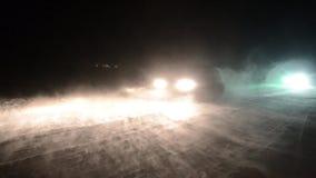 Los coches están conduciendo en un camino del invierno en una ventisca de las nevadas fuertes en la noche Camino peligroso del in almacen de metraje de vídeo