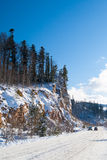 Los coches están en el camino de la montaña del invierno en de Adygea Imagen de archivo libre de regalías