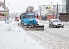 Los coches limpian nieve imagenes de archivo