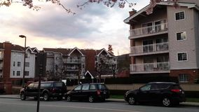 Los coches montan por la calle con el edificio en el tiempo de primavera metrajes