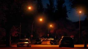 Los coches pasan con área residencial en la noche almacen de video