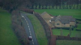 Los coches pasan la casa de la granja en paisaje rural almacen de metraje de vídeo