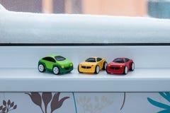 Los coches plásticos del juguete acercan a la ventana nevada Imagen de archivo libre de regalías