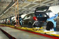 Los coches se colocan en la línea del transportador de nave de montaje Automóvil favorable Imagen de archivo libre de regalías
