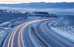 Los coches se encienden en la carretera en tiempo de mañana Fotos de archivo