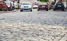Los coches van en los adoquines del camino Fotografía de archivo libre de regalías