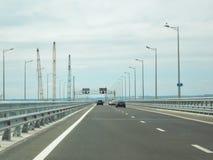 Los coches van en un nuevo puente ancho del camino imagen de archivo