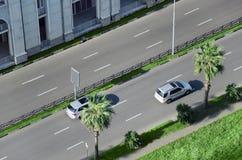 Los coches van por el camino en la calle de la ciudad dividida por los espacios y las palmeras verdes Fotografía de archivo libre de regalías