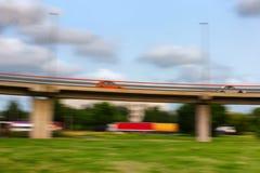Los coches van rápidamente en un puente en un día de verano blurry foto de archivo