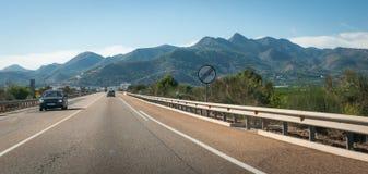 Los coches viajan en automóvili abajo de la carretera a través de las colinas y de las montañas costeras de España Imagen de archivo