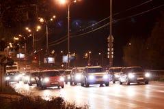 Los coches y el otro transporte en la ciudad de la noche Imagenes de archivo