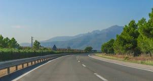 Los coches y los camiones viajan en automóvili abajo de la carretera a través de las colinas y de las montañas costeras de España Fotografía de archivo libre de regalías