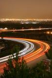 Los coches y los carros enfocan abajo de la carretera Foto de archivo