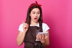 Los cocineros de sexo femenino del ama de casa, vistieron el delantal marrón, camiseta blanca, hairband rojo en fondo rosado La m imagen de archivo